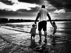 Un papa avec ses enfants à la mer, en noir et blanc