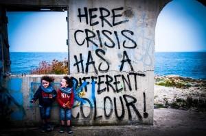 """Enfants devant un tag """"Here crisis has a different colour"""""""
